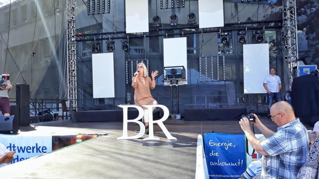 Brunhilde Rieber bringt das zahlreich erschienene Publikum vor dem Start ihrer großen Modenschau erst einmal kurz auf den neuesten Stand.