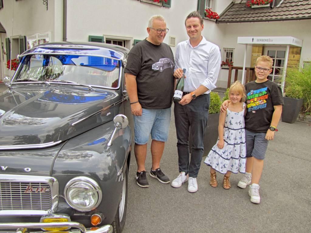 Björn Mündelein (2.v.l.) empfiehlt Jörg Müller, der das Haus Gerbens mit seinen Enkeln Martha und Noah in seinem legendären Buckelvolvo besucht, einen erlesenen Wein, den es auch am Weinstand von Haus Gerbens auf dem Fest geben wird.